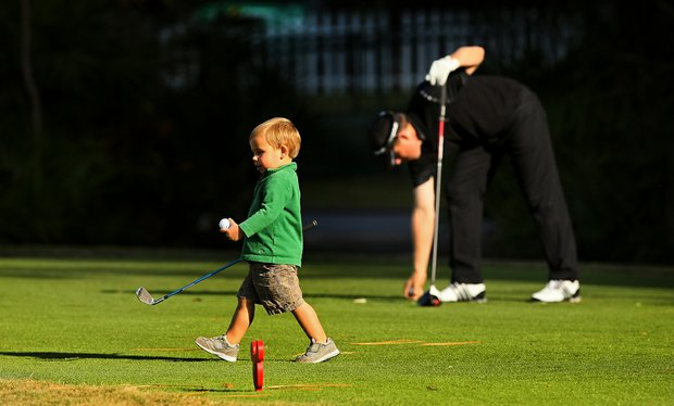 Sky Leonard, 2, walks off the tee box as his dad, PGA Tour player, Justin Leonard prepares to hit his tee shot during the PGA Tour Father/Child Tournament on the Oak Trail Course.