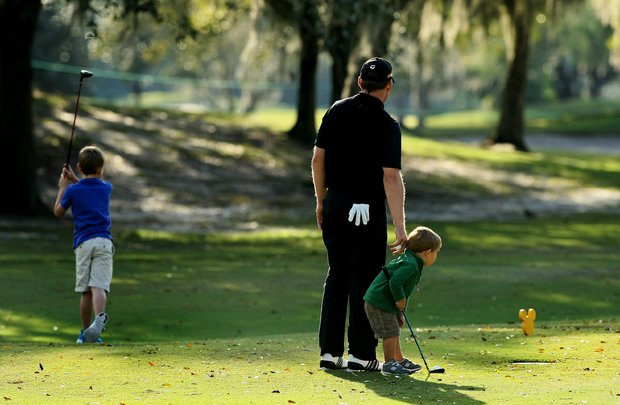 PGA Tour player Justin Leonard holds on to his son, Sky, 2, while his son Luke, 6, tees off during the PGA Tour Father/Child Tournament on the Oak Trail Course.