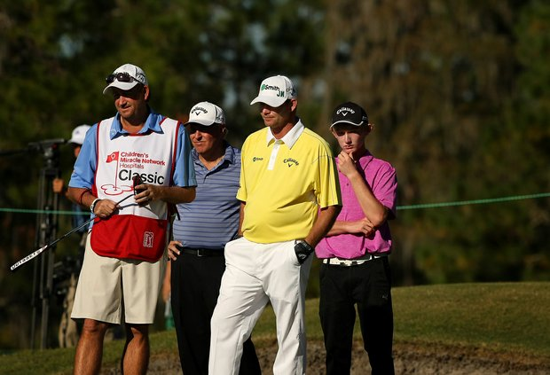 Pro- Am participant J. J. Qualkenbush, 16, stands behind Tommy Gainey at No. 14 on the Magnolia Course during the Children's Miracle Network Hospitals Classic.