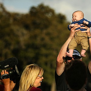Charlie Beljan holds up his son, Graham, 2 months, after winning the Children's Miracle Network Hospitals Classic.