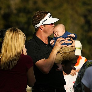 Charlie Beljan kisses his 2-month old son Graham after winning the Children's Miracle Network Hospitals Classic.