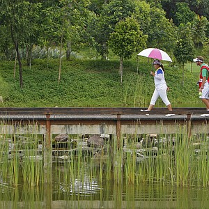 Inbee Park, left, of South Korea crosses a bridge with her caddie on the 14th hole during the final round of the LPGA Malaysia golf tournament at Kuala Lumpur Golf and Country Club in Kuala Lumpur, Malaysia, Sunday, Oct. 14, 2012. Park won the LPGA Malaysia golf tournament with the score 15-under-par 269.