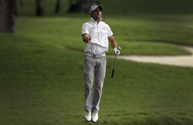 Jbe Kruger of South Africa jumps to get a better look at the green on the eighteenth hole during the Singapore Open golf tournament at the Serapong Course at Sentosa Golf Club in Singapore on Friday Nov. 9, 2012.