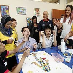 Golfer Michelle Wie, second from right, of the United States greets to an autistic boy at Creative Arts Centre for autistic children during its launch in Shah Alam, outside Kuala Lumpur, Malaysia, Monday, Oct. 8, 2012.
