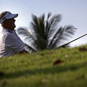 Colin Montgomerie of Scotland is silhouetted as he tees off on the 13th hole during the first round of the Singapore Open golf tournament at the Serapong Course at Sentosa Golf Club in Singapore on Thursday, Nov. 8, 2012.