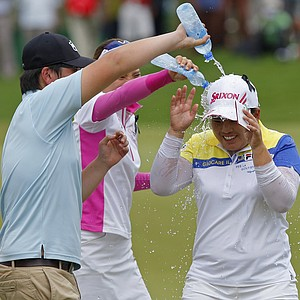 Inbee Park, right, of South Korea is splashed with water after winning the LPGA Malaysia golf tournament at Kuala Lumpur Golf and Country Club in Kuala Lumpur, Malaysia, Sunday, Oct. 14, 2012.