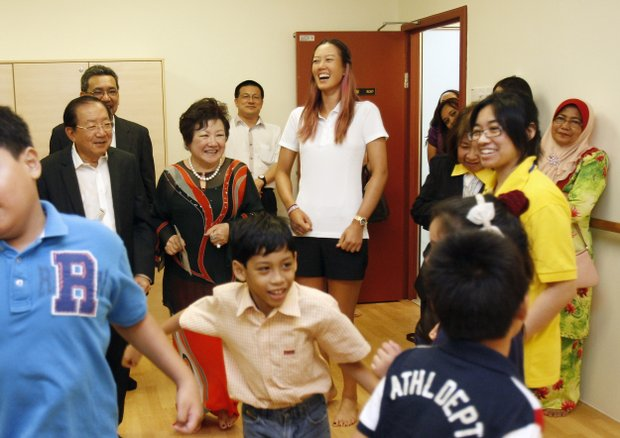 Golfer Michelle Wie, center, of the United States laughs as she plays a game with autistic children at Creative Arts Centre for autistic children during its launch in Shah Alam, outside Kuala Lumpur, Malaysia, Monday, Oct. 8, 2012.
