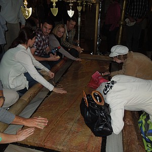 Michael Thompson, far left, and Hunter Mahan, middle, touch the stone where the body of Christ is believed to have rested after he was taken off the cross.