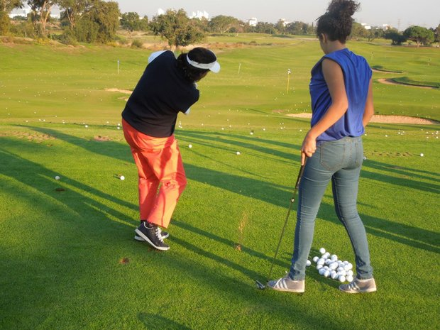 Amy Alcott shows Doha Alma the proper swing technique.