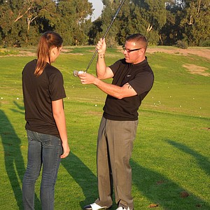 Sean Foley shows the sweet spot to a rookie golfer from Peace Players.