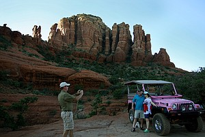 Matt Auberle with Pink Jeep Tours taking a picture of tourists on The famous Red Rocks in the Coconino National Forest in Sedona, AZ via the Pink Jeep Tour.