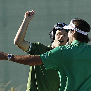 Ben Crane, rear, and Bubba Watson sing to the crowd at the 16th hole after they hit their tee shots during the third round of the Phoenix Open golf tournament Saturday, Feb. 4, 2012, in Scottsdale, Ariz.