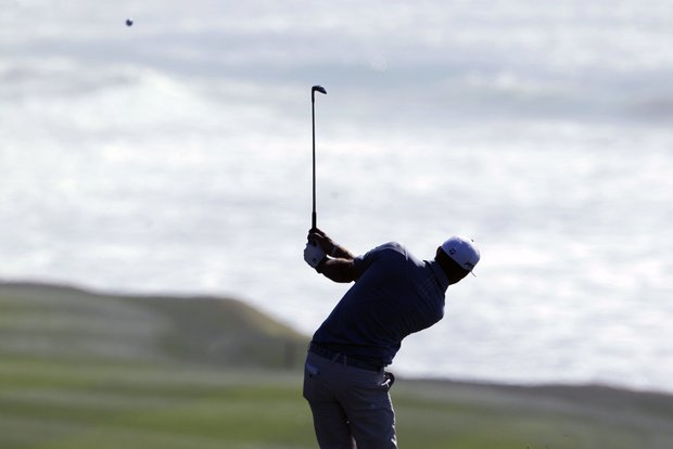 Dustin Johnson hits from the ninth fairway of the Pebble Beach Golf Links during the first round of the AT&T Pebble Beach National Pro-Am PGA Tour golf tournament in Pebble Beach, Calif., Thursday, Feb. 9, 2012. Johnson is tied for the lead with two others after shooting a 9-under-par 63.