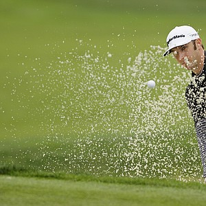 Dustin Johnson blasts out of bunker to the first green of the Monterey Peninusla Country Club shore course during the third round of the AT&T Pebble Beach National Pro-Am golf tournament in Pebble Beach, Calif., Saturday, Feb. 11, 2012.