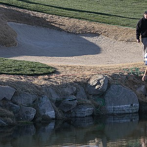Dustin Johnson checks out his lie on the edge of a water hazard on the third hole during the Match Play Championship golf tournament, Wednesday, Feb. 22, 2012, in Marana, Ariz. Johnson conceded the hole to Ryo Ishikawa.