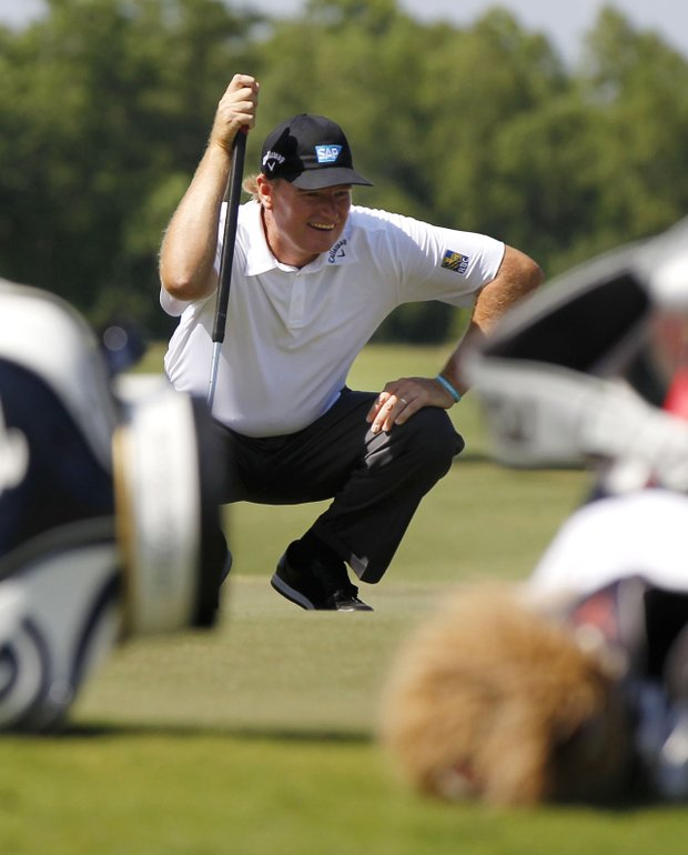 Ernie Els is framed by golf bags as he lines up a shot in the 11th green during the first round of the Zurich Classic golf tournament at TPC Louisiana in Avondale, La., Thursday, April 26, 2012.