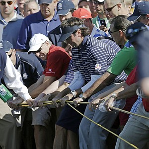 USA's Bubba Watson helps move some cables before a shot on the 14th hole during a foursomes match at the Ryder Cup PGA golf tournament Saturday, Sept. 29, 2012, at the Medinah Country Club in Medinah, Ill.