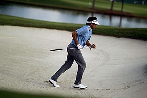 Bubba Watson runs out of the sand trap after hitting his ball onto the green on the 18th hole in the first round of the Tour Championship golf tournament Thursday, Sept. 20, 2012, in Atlanta.