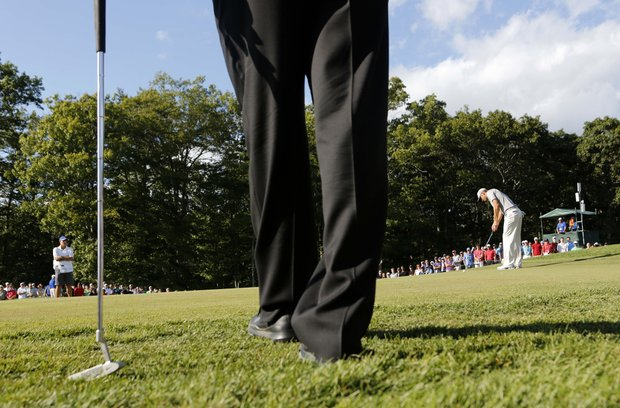 Tiger Woods, foreground, waits while Dustin Johnson, right, putts on the 15th hole during the final round of the Deutsche Bank Championship PGA golf tournament at TPC Boston in Norton, Mass., Monday, Sept. 3, 2012.