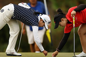 Moriya Jutanugarn, right, of Thailand marks her ball as Ayako Uehara of Japan repairs a ball mark at No. 4 on Champions course.