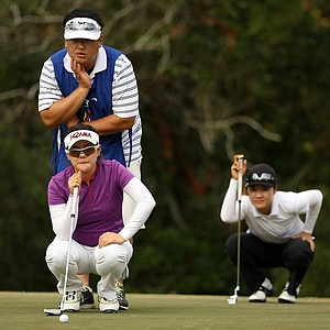 Eunjung Yi and Na On Min look over their putts at No. 3 on Legends course during Saturday of LPGA Q-School.