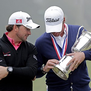 Webb Simpson shows the championship trophy to Graeme McDowell, of Northern Ireland, after the U.S. Open Championship golf tournament Sunday, June 17, 2012, at The Olympic Club in San Francisco.