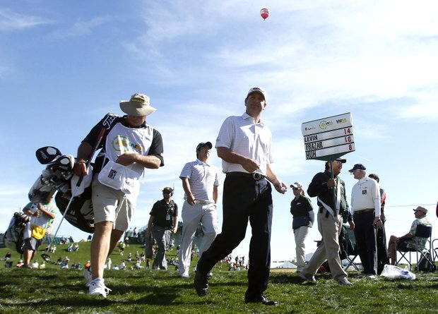 Harrison Frazar, front, walks with caddie Marcel LeBas, far left, and golfer John Huh, back middle, as both chase tournament leader Spencer Levin as they exit the second hole during the third round of the Phoenix Open golf tournament Saturday, Feb. 4, 2012, in Scottsdale, Ariz.