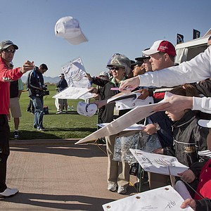Australia's Adam Scott, left, tosses a hat back to a fan while signing autographs before practicing for the Match Play Championship, Monday, Feb. 20, 2012, in Marana, Ariz.