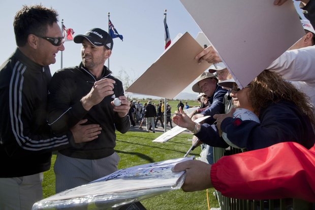 Spain's Sergio Garcia is greeted by a friend while signing autographs for fans during a practice session for the Match Play Championship, Monday, Feb. 20, 2012, in Marana, Ariz.