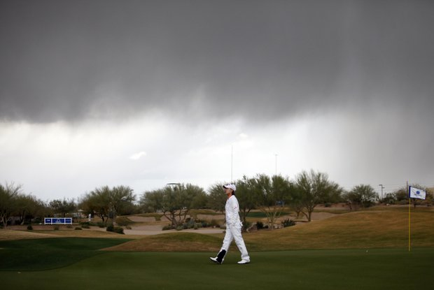 Na Yeon Choi, of South Korea, walks off the 14th green after play was suspended due to inclement weather for the third time of the day, during the final round of the LPGA Founders Cup golf tournament Sunday, March 18, 2012, in Phoenix.