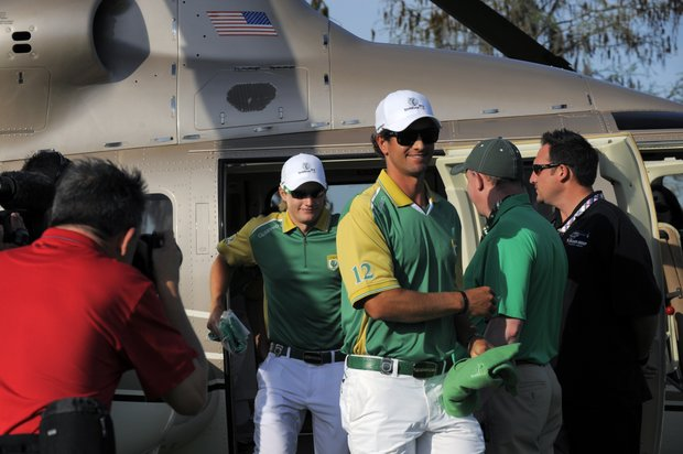 Team Queenwood's Adam Scott, center right, of Australia, and Tom Lewis arrive on the 18th green via helicopter before the start of the two-day Tavistock Cup exhibition golf tournament at Lake Nona Golf & Country Club Tuesday, March 20, 2012, in Orlando, Fla.