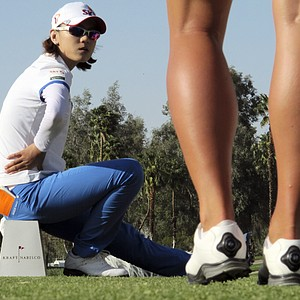 Na Yeon Choi, of South Korea, left, talks with Karin Sjodin, of Sweden, on the 18th tee during the third round of the LPGA Kraft Nabisco Championship golf tournament in Rancho Mirage, Calif., Saturday, March 31, 2012.