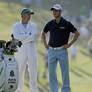 Martin Kaymer, of Germany, talks to his caddie Christain Donald before hitting on the first fairway during the first round of the Masters golf tournament Thursday, April 5, 2012, in Augusta, Ga.