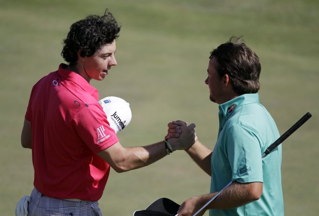 Rory McIlroy, left, of Northern Ireland, shakes hands with Graeme McDowell, of Northern Ireland, following their fourth round of the Masters golf tournament Sunday, April 8, 2012, in Augusta, Ga.