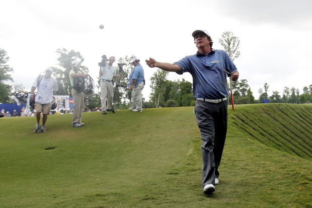 Jason Dufner tosses a ball to his caddie as he walks off the ninth green during the final round of the Zurich Classic golf tournament at TPC Louisiana in Avondale, La., Sunday, April 29, 2012.