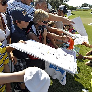 Rickie Folwer, right, signs autographs after completing a practice round for The Players Championship golf tournament Wednesday, May 9, 2012, at Sawgrass in Ponte Vedra Beach, Fla.