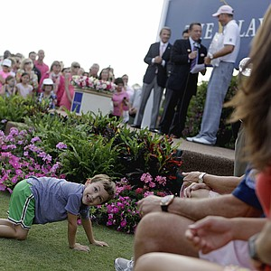 Cameron Kuchar, 4, crawls on the ground as his father Matt Kuchar, on stage at right, is presented with the championship trophy after winning The Players Championship golf tournament Sunday, May 13, 2012, at TPC Sawgrass in Ponte Vedra Beach, Fla.