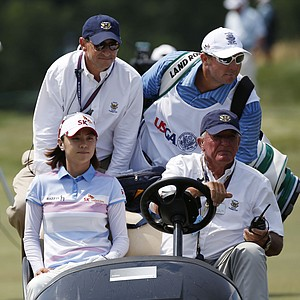 Na Yeon Choi, front left, of South Korea, rides back to the 10th tee after hitting her first shot out of bounds during the final round the U.S. Women's Open golf tournament on Sunday, July 8, 2012, in Kohler, Wis.