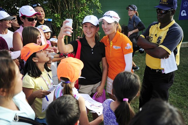 Steffi Yo, 16, center left, of Tampa, Fla., takes a picture with golfer So Yeon Ryu, as others clamor for autographs at the Twin Eagles Club Eagle Course, Sunday, Nov. 18, 2012, in Naples, Fla. Na Yeon Choi, of South Korea, won the tournament. She closed with two pars for a 2-under 70 and a two-shot victory over Ryu.