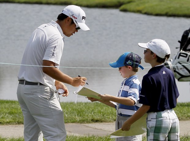 John Huh, left, signs an autograph during a practice round for the BMW Championship PGA golf tournament at Crooked Stick Golf Club in Carmel, Ind., Tuesday, Sept. 4, 2012.