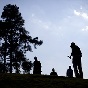 Matt Kuchar, right, walks up the green after chipping out of the rough as Dustin Johnson, left, walks over to his ball followed by caddies on the 17th hole during the third round of the Tour Championship golf tournament on Saturday, Sept. 22, 2012, in Atlanta.