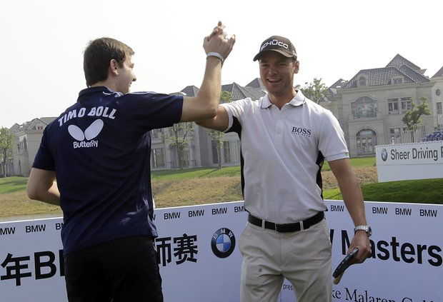 German table tennis player Timo Boll, left, and Martin Kaymer of Germany, right, greet each other after playing ping pong during the photo opportunities, ahead of the Masters golf tournament in Shanghai, China Monday Oct. 23, 2012.