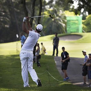 Spectators watch as Adam Scott of Australia hits the ball out of the rough on the 15th hole during the first round of the Singapore Open golf tournament at the Serapong Course at Sentosa Golf Club in Singapore on Thursday, Nov. 8, 2012.