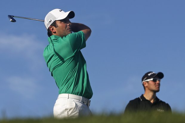 Francesco Molinari, from Italy, plays a shot from the 13th tee as Martin Kaymer, right, from Germany, follows the path of the ball during the first round of the Portugal Master golf tournament at the Victoria golf course in Vilamoura, southern Portugal, Thursday, Oct. 11, 2012.