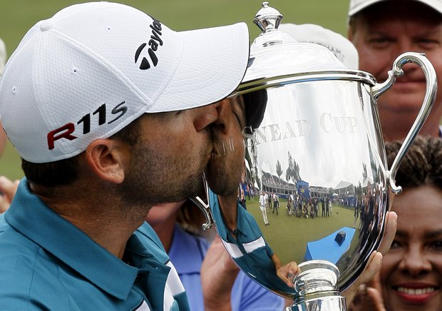 Sergio Garcia, of Spain, kisses the Sam Snead Cup after winning the rain delayed Wyndham Championship golf tournament in Greensboro, N.C., Monday, Aug. 20, 2012.