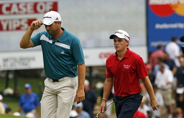 Sergio Garcia, left, and Bud Cauley approach the 18th green during the final round of the rain delayed Wyndham Championship golf tournament in Greensboro, N.C., Monday, Aug. 20, 2012.