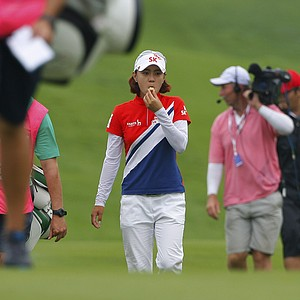 Na Yeon Choi, center, of South Korea eats biscuit as she walks on the 9th hole during the third round of the LPGA Malaysia golf tournament at Kuala Lumpur Golf and Country Club in Kuala Lumpur, Malaysia, Saturday, Oct. 13, 2012.