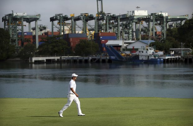 Adam Scott of Australia walks along the fairway of the 15th hole with the Singapore Port in the background during the first round of the Singapore Open golf tournament at the Serapong Course at Sentosa Golf Club in Singapore on Thursday, Nov. 8, 2012.