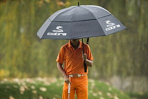 Rickie Fowler protects himself from the rain while waiting to put on the fourth hole during the final round of the World Challenge golf tournament at Sherwood Country Club in Thousand Oaks, Calif., Saturday, Dec. 2, 2012.