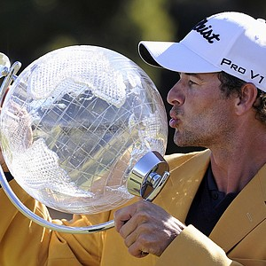 Adam Scott from Australia kisses the trophy as he poses for photographers after winning the Australian Masters golf tournament at Kingston Heath Golf Club in Melbourne, Australia, on Sunday, Nov. 18, 2012.